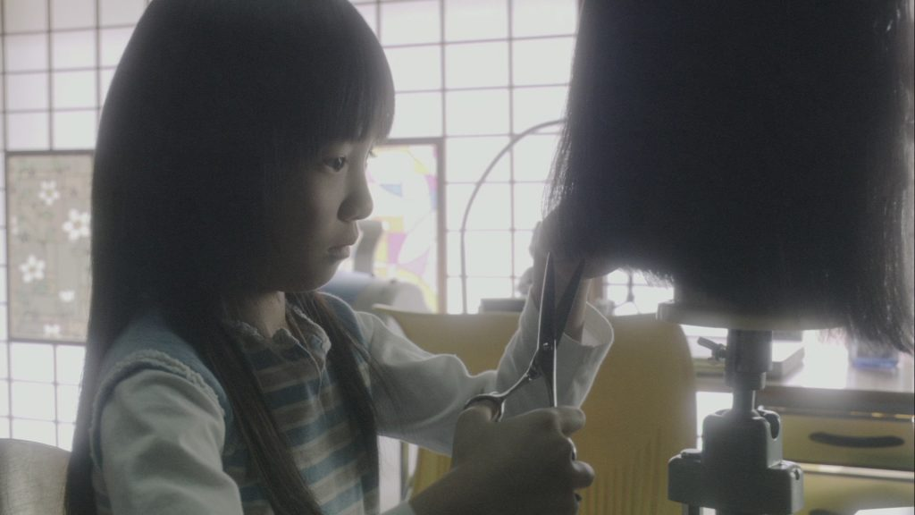 Mami, la nièce de Yûki, s'exerce à l'art de la coiffure.