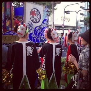 Trois personnes portent le masque du kitsune dans un matsuri