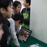 De jeunes fans de Chihayafuru observent la photo de l'équipe du film au centre de karuta du sanctuaire Ômi